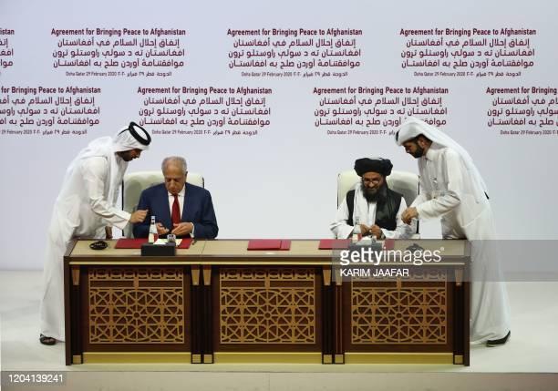 US Special Representative for Afghanistan Reconciliation Zalmay Khalilzad and Taliban cofounder Mullah Abdul Ghani Baradar sign a peace agreement...