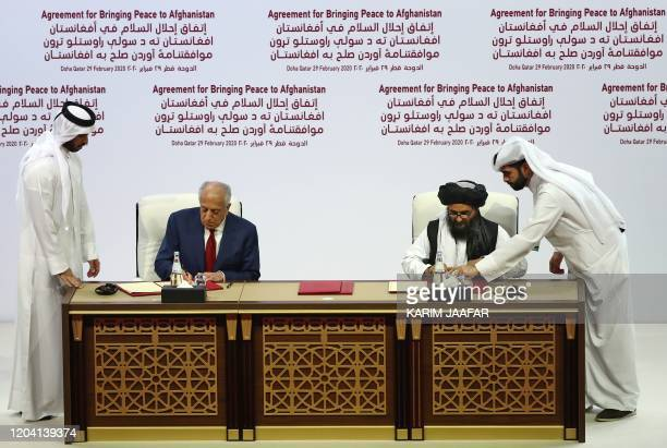 Special Representative for Afghanistan Reconciliation Zalmay Khalilzad and Taliban co-founder Mullah Abdul Ghani Baradar sign a peace agreement...