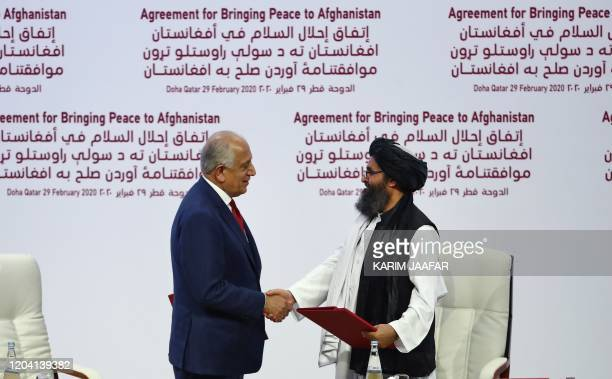 US Special Representative for Afghanistan Reconciliation Zalmay Khalilzad and Taliban cofounder Mullah Abdul Ghani Baradar shake hands after signing...