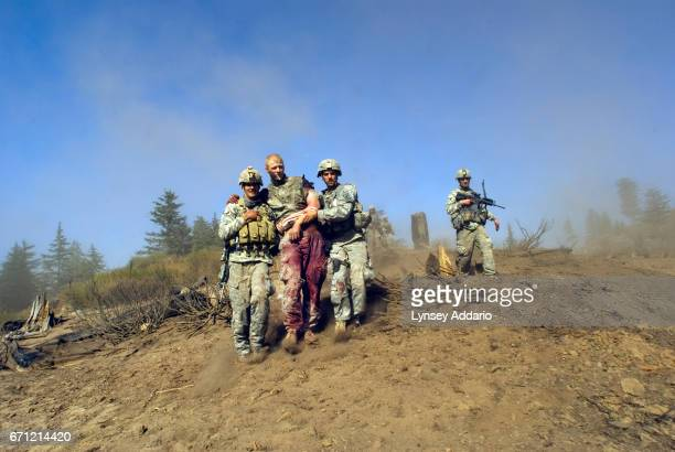 VALLEY AFGHANISTAN Specialist Carl Vandeberge center and Sergeant Kevin Rice behind are assisted as they walk to a medevac helicopter minutes after...