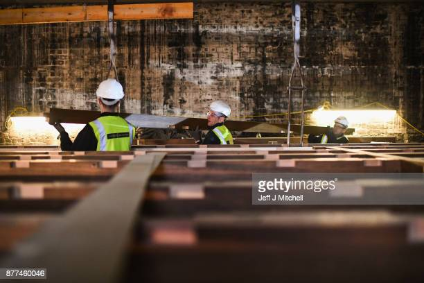 Specialist carpenters from Lawrence McIntosh hold a beam as they install the floor to the bookstore above the Mackintosh Library on November 22 2017...