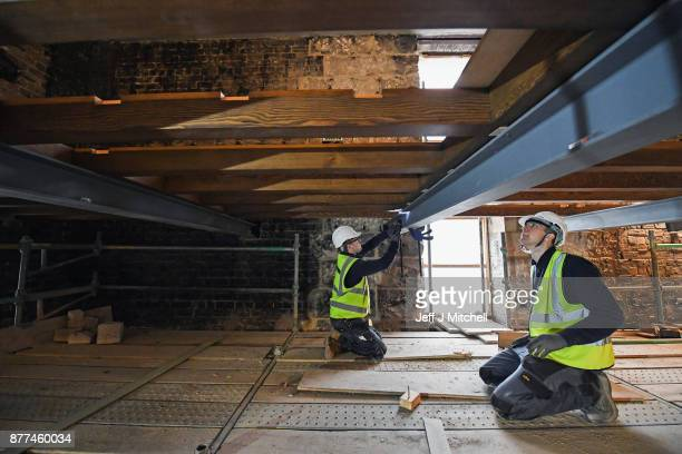 Specialist carpenters from Lawrence McIntosh put a beam into place as they install the floor to the bookstore above the Mackintosh Library on...