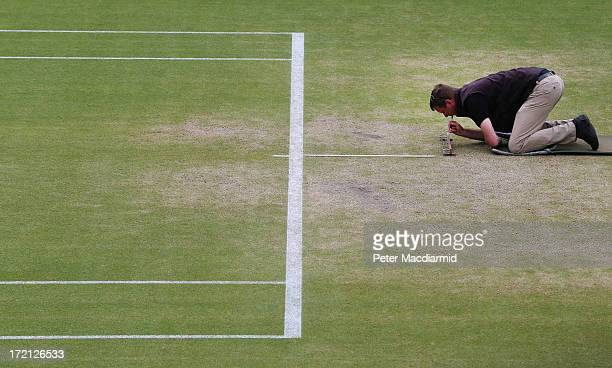 A specialist checks the density of blades of the grass of Centre Court at the Wimbledon Lawn Tennis Championships on July 1 2013 in London England...