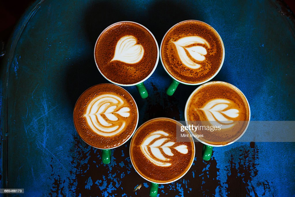 Specialist coffee shop. Cups of coffee with patterns in the froth on the top. : Stock Photo