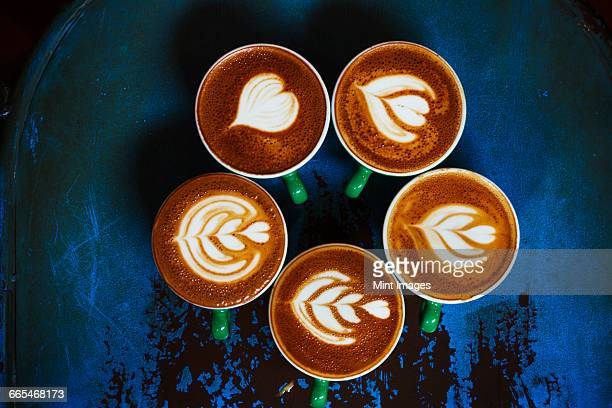 Specialist coffee shop. Cups of coffee with patterns in the froth on the top.