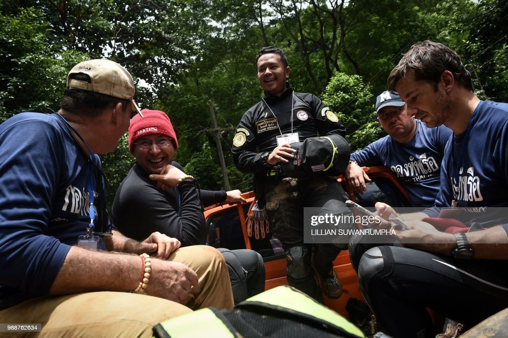 Specialist divers from the US, Russia and Belgium chat before being escorted by a Thai rescue worker to Tham Luang cave, at the Khun Nam Nang Non Forest Park in the Mae Sai district of Chiang Rai province on July 1, 2018, as the rescue operation continues for a missing children's football team and their coach. - Twelve Thai boys and their assistant football coach spent their eighth night trapped in a flooded cave, as a round-the-clock search was aided by better weather on July 1.
