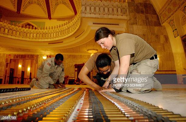 Specialist Erin Kotchian Private 2nd class Idalissa Sowards and Corporal Barry Page of the 720 Military Police Batallion count ammunition as they and...