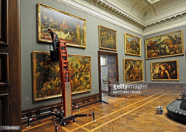 A specialist inspects the painting Stillleben mit einem Bauernpaar by Flamish artist Frans Snyders at the Old Masters Picture Gallery in Dresden...