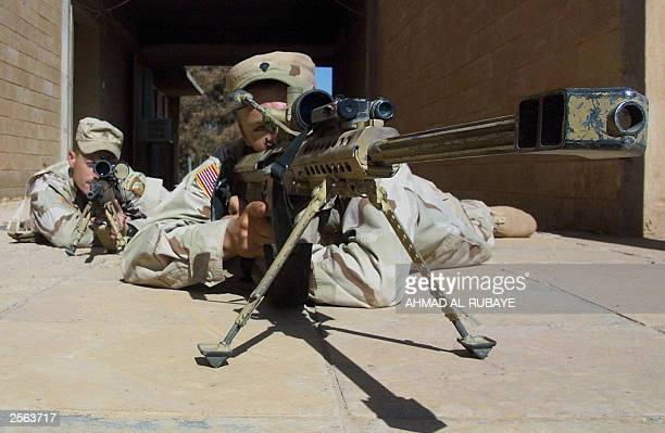 Specialist Jacob Sprenger from Nebraska, takes up position with his 50 caliber sniper's semi-automatic ahead of Sergeant Brian Stinson from Kentucky...