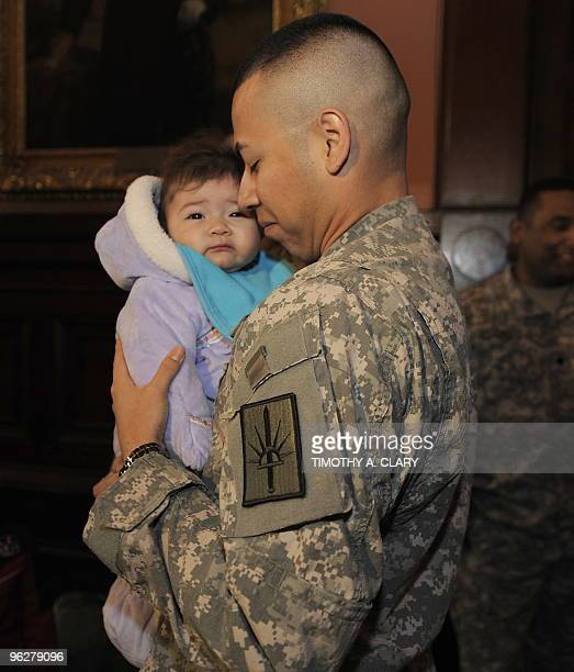 Specialist Jesus Aquino of the New York Army National Guard's 53rd Army Liaison Team who have spent the past year in Iraq hugs his daughter Amy as...