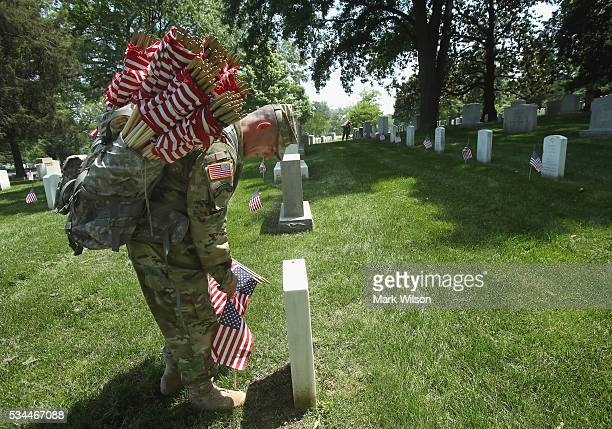 Specialist Jose Barreiro of the 3rd US Infantry Regiment 'The Old Guard' places a flag at a grave site during the 'FlagsIn' ceremony May 26 2016 at...