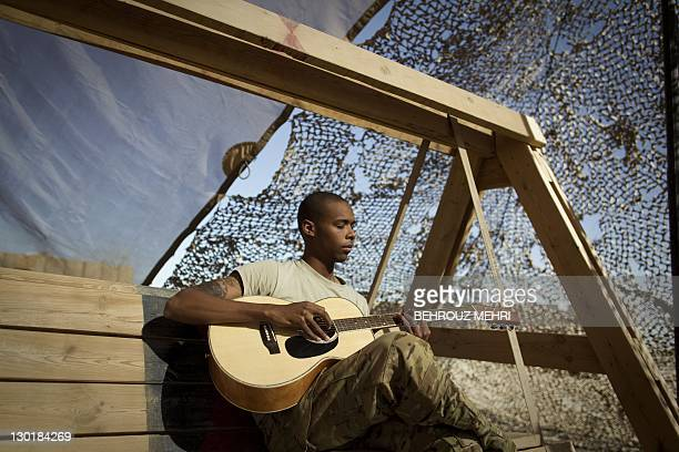 US specialist Keneth Horton from the US Army's Task Force Lift Dust Off Charlie Company 4101 Aviation Regiment plays guitar in Forward Operating Base...