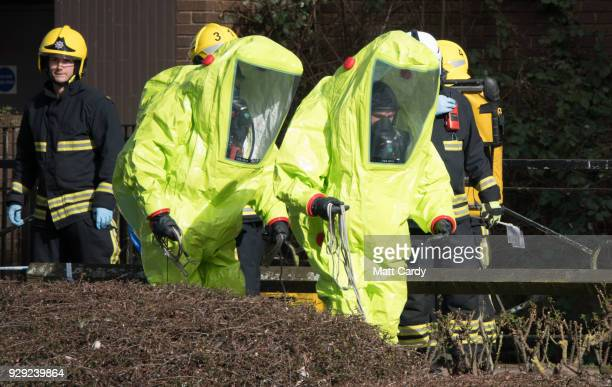 Specialist officers in protective suits prepare to secure the police forensic tent that had been blown over by the wind and is covering the bench...