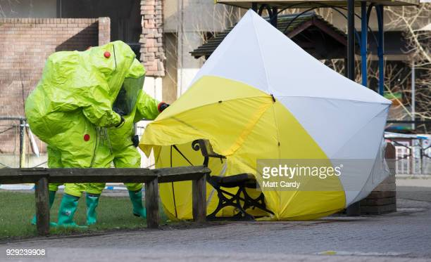 Specialist officers in protective suits secure the police forensic tent that had been blown over by the wind and is covering the bench where Sergei...