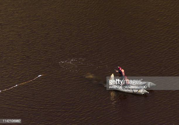 A specialist on a boat equipped with a sonar system inspects an object from the acidic Red Lake near the village of Mitsero southwest of the capital...