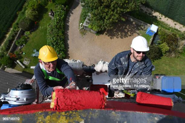 Specialist painters Frank Windass and Mark Hairsine work on Happisburgh Lighthouse near Cromer in Norfolk as it is repainted with its iconic red and...