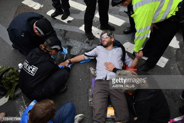 Specialist police officers unglue a climate activists from the Extinction Rebellion group from the street blocking London Bridge in central London on...