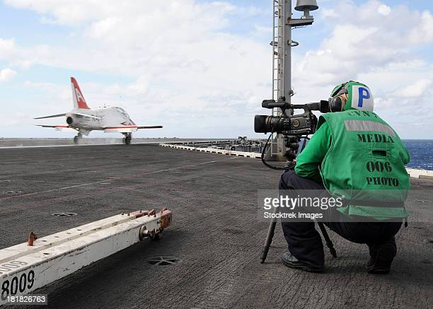 Specialist records video of flight deck operations.