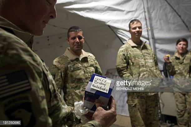 US specialist Robert D Hardisty from US Army's Task Force Lift Dust Off Charlie Company 1171 Aviation Regiment looks at his 25th birthday gift of...