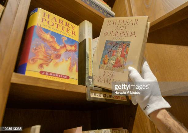 Specialist Rui Moutinho reaches for an autographed copy of Baltasar and Belinda at Sala Gemma in Lello Bookstore on the eve of its 113th anniversary...