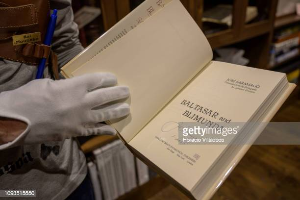 Specialist Rui Moutinho shows an autographed copy of Jose Saramago's Baltasar and Blimunda at Sala Gemma in Lello Bookstore on the eve of its 113th...