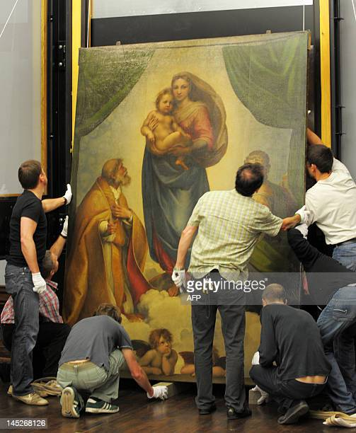 Specialists hang the Sistine Madonna by Raphael in the Old Masters Gallery in Dresden, eastern Germany on May 23, 2012. A special exhibition in the...