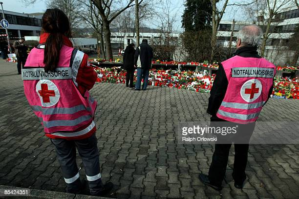 Specially trained members of the Red Cross stand near mourners visiting outside the local high school on March 14 2009 in Winnenden Germany 17 year...