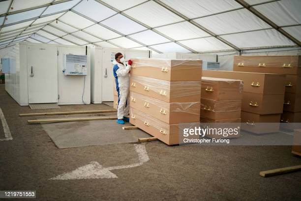 Specially trained volunteer and mosque trustee Mohammed Zahid works at the temporary mortuary erected in the car park of Central Jamia Mosque Ghamkol...