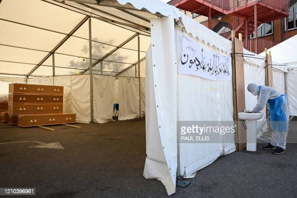 A specially trained volunteer washes his hands as preparation for burials continues at a temporary mortuary set up in the car park of Central Jamia...