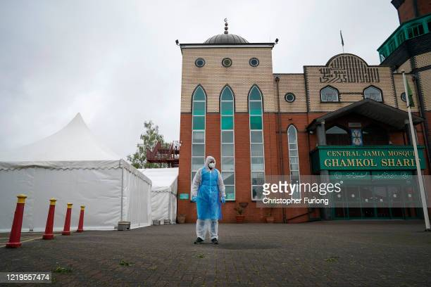 Specially trained volunteers work at a temporary mortuary erected in the car park of Central Jamia Mosque Ghamkol Sharif on April 18, 2020 in...