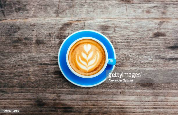 specialty coffee with foam latte art served in blue cup, directly from above - kaffee getränk stock-fotos und bilder