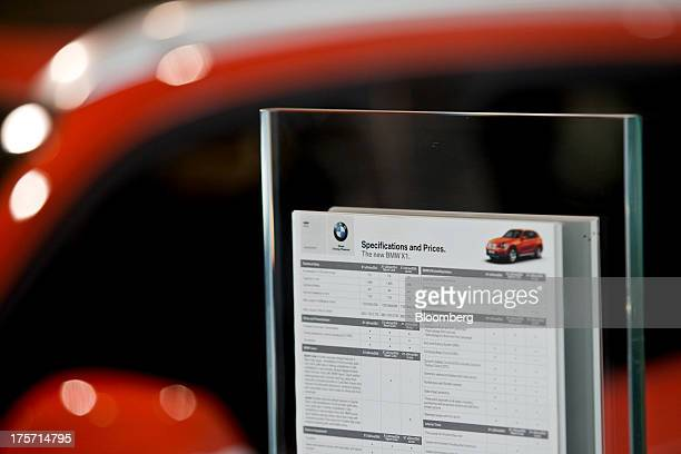 A specifications and pricing guide for a Bayerische Motoren Werke AG X1S vehicle is displayed at the Deutsche Motoren BMW dealership in Faridabad...