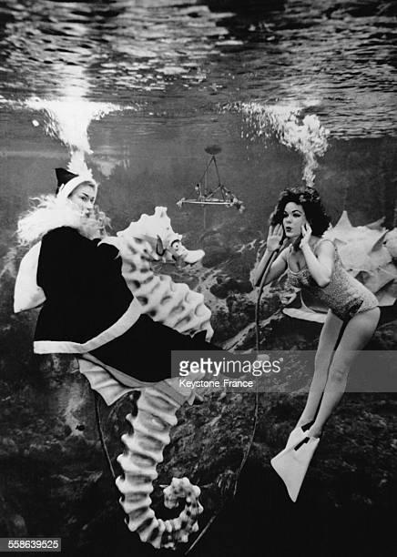 Spectacle de danse aquatique mettant en scene un Pere Noel chevauchant un immense hippocampe, a Miami, Floride, le 24 decembre 1962.
