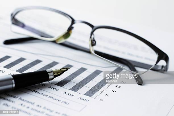 spectacles and pen on top of a bar chart document - credit union stock photos and pictures
