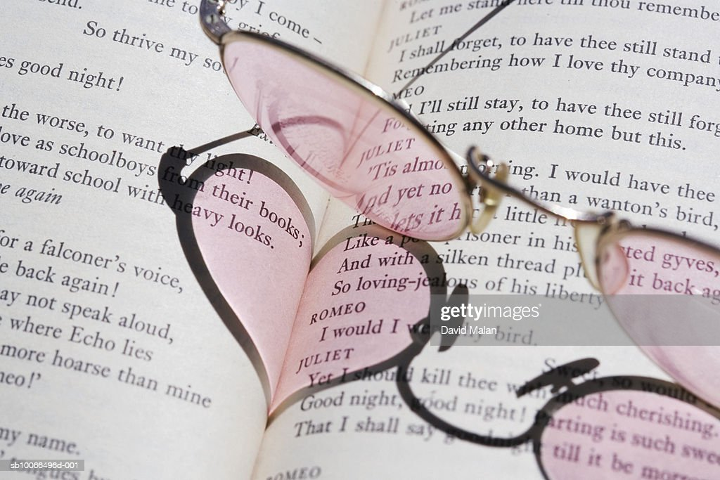 Spectacles Casting Heart Shaped Shadow Onto Open Book Stock Photo