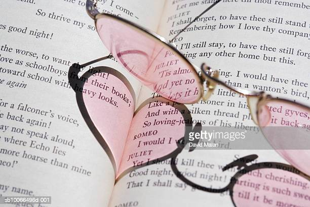 Spectacles casting heart shaped shadow onto open book