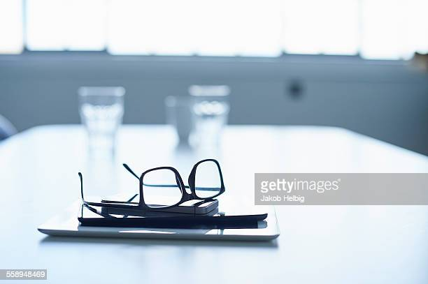 Spectacles, digital tablet and smartphone on conference table