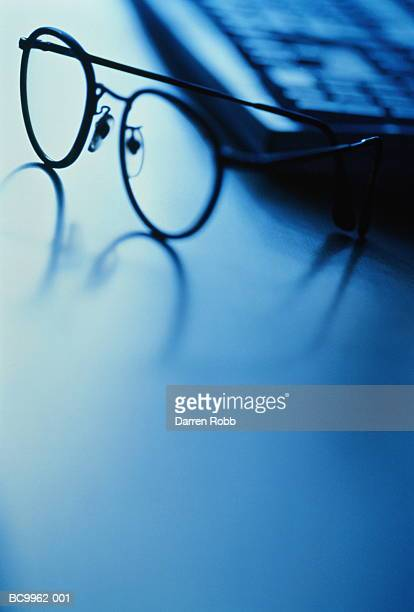 spectacles in front of keyboard, close-up (toned b&w) - toned image stock pictures, royalty-free photos & images