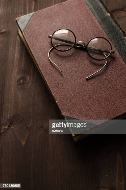 Spectacles on a book on wooden table