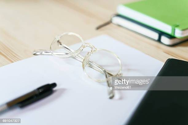 Spectacles on a sheet of paper on desk with notebooks and pen