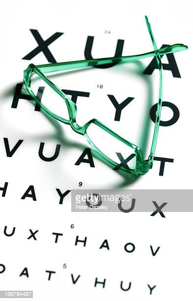 Spectacles on optician's eye test chart
