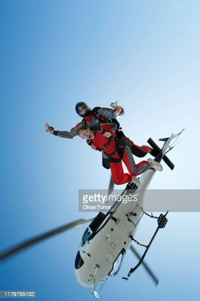 spectacular jump out of a helicopter from a tandem skydiving couple. the passenger is super thrilled to dive into the free fall. - lauterbrunnen - fotografias e filmes do acervo