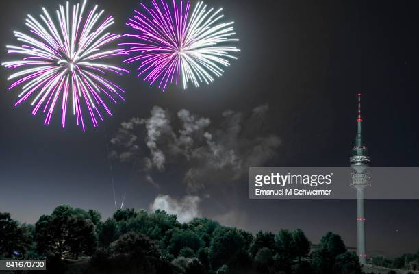 spectacular, majestic fireworks display with colorful starburst explosives exploding in the night sky, rockets shot up bursting, glowing, sparkling and streaking lights during summer festival with munich's . tv tower in background illuminated - olympischer park veranstaltungsort stock-fotos und bilder