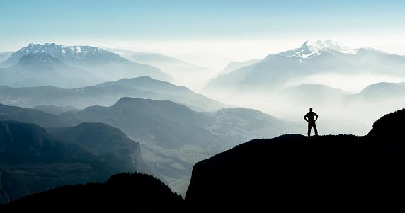 Spectacular mountain ranges silhouettes. Man reaching summit enjoying freedom. 926199536