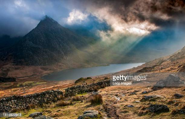 Spectacular stormy light over Tryfan and Llyn Ogwen from the slopes of Pen yr Ole Wen in Snowdonia.