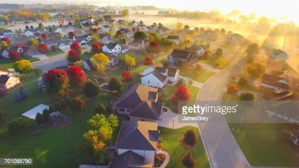 Spectacular sunbeams through fog in autumn neighborhood, aerial view.
