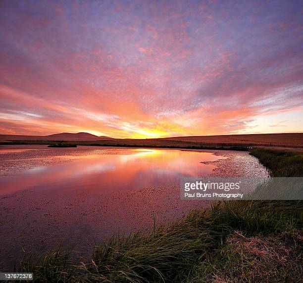 Spectacular sunset sky reflected in farm dam