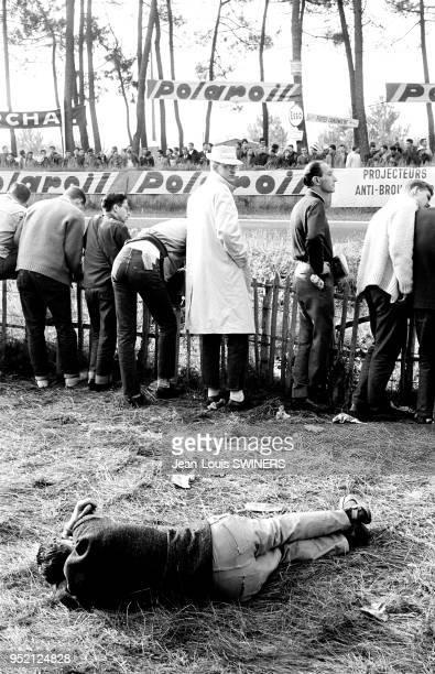 Spectateur dormant allongé sur le sol au bord du circuit des 24 Heures du Mans en juin 1962 dans la Sarthe France