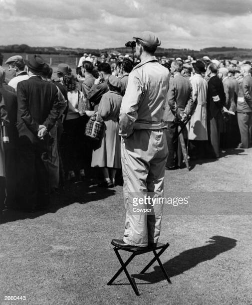 A spectator at the Open Golf championship at Carnoustie standing on a stool so he can see over the heads of the other fans