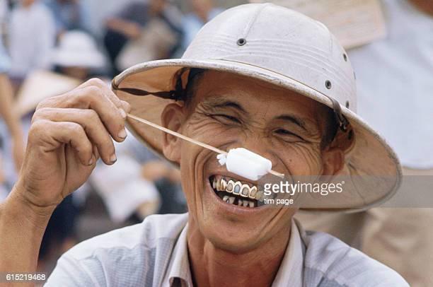 A spectator at the Phu Tho Racecourse in Saigon enjoys an ice lolly Vietnam 1968 | Location Phu Tho Racecourse Saigon Vietnam